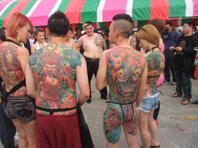 不少年轻男女刺青模特在广场展示身上的纹身,让游客拍照.