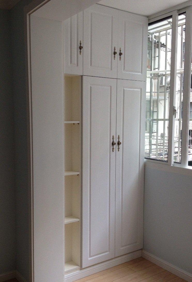 浅色衣柜,阳台是满门,门是红色,床深灰色,白色墙面,黄色地板.图片